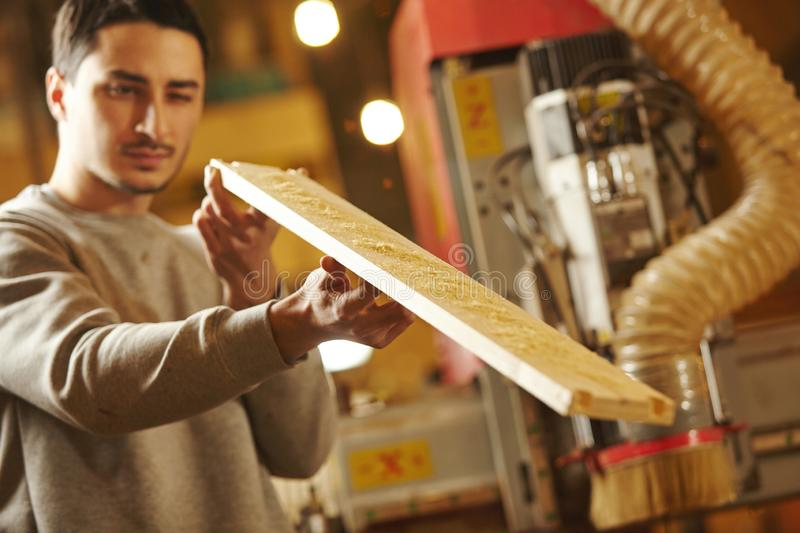 Man checks the evenness of grinding wood after CNC machine. royalty free stock photo
