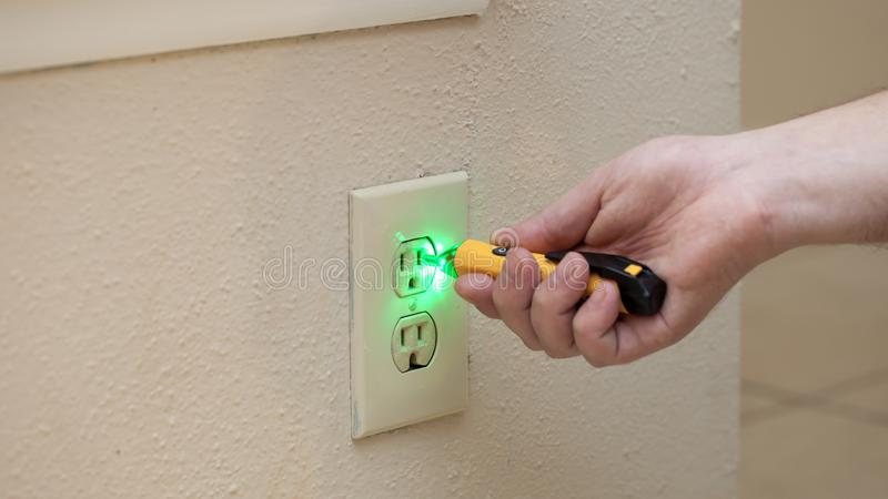 Man checks if there is power in wall socket with tool stock images