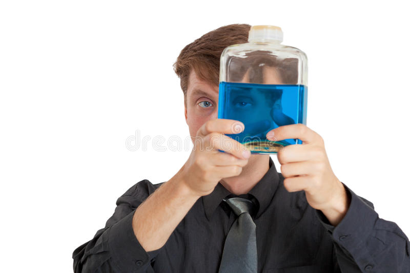 Man checks physical properties of liquid in bottle