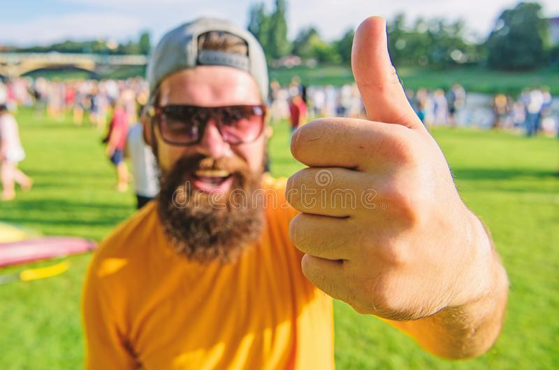 Man cheerful face shows thumb up. Man bearded in front of crowd riverside background. Top list summer festival must. Visit. Highly recommend top list. Hipster royalty free stock photography