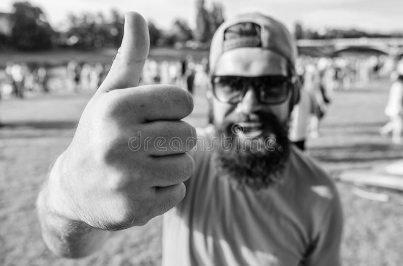 Man cheerful face shows thumb up. Man bearded in front of crowd riverside background. Top list summer festival must. Visit. Highly recommend top list. Hipster royalty free stock photos