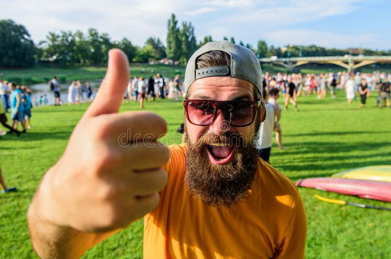 Man cheerful face shows thumb up. Man bearded in front of crowd riverside background. Top list summer festival must. Visit. Hipster visiting event picnic fest royalty free stock image