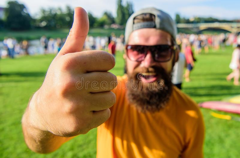 Man cheerful face shows thumb up. Man bearded in front of crowd riverside background. Top list summer festival must. Visit. Highly recommend top list. Hipster royalty free stock photo