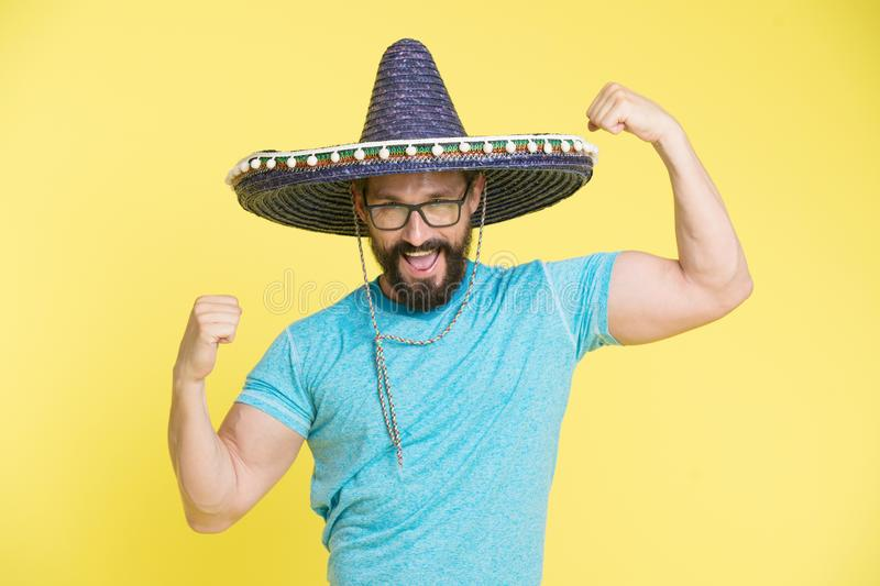 Man cheerful face in sombrero hat posing with biceps muscles strong gesture yellow background. Mexican party concept stock photos