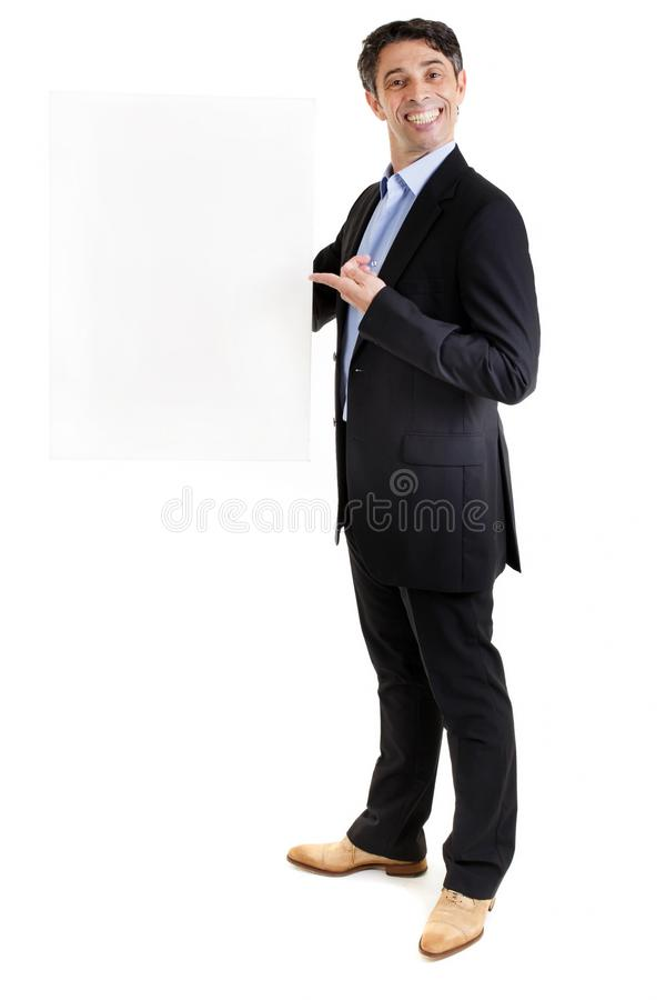 Man with a cheesy grin holding a blank sign. Suave businessman or salesman with an insincere cheesy toothy grin holding a blank sign and pointing to it with his stock photography