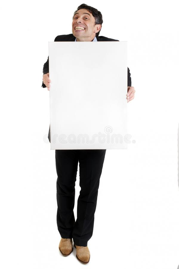 Man with a cheesy grin holding. Businessman with a cheesy toothy grin of insincerity and obsequiousness holding a blank white sign with copyspace for your text stock photo