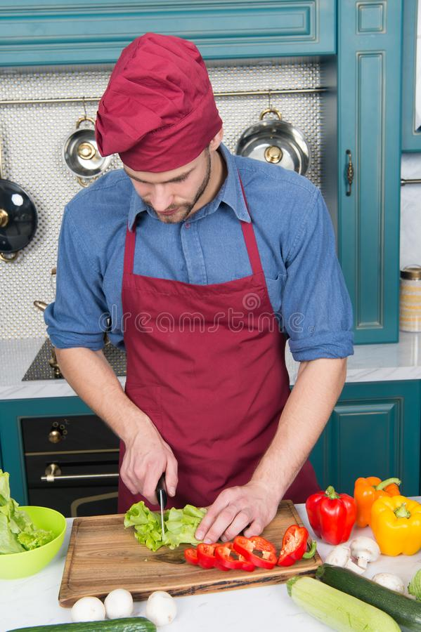 Man chef cook food following recipe in restaurant kitchen. Man chef cut vegetables. Best cooking recipe from chef royalty free stock photo