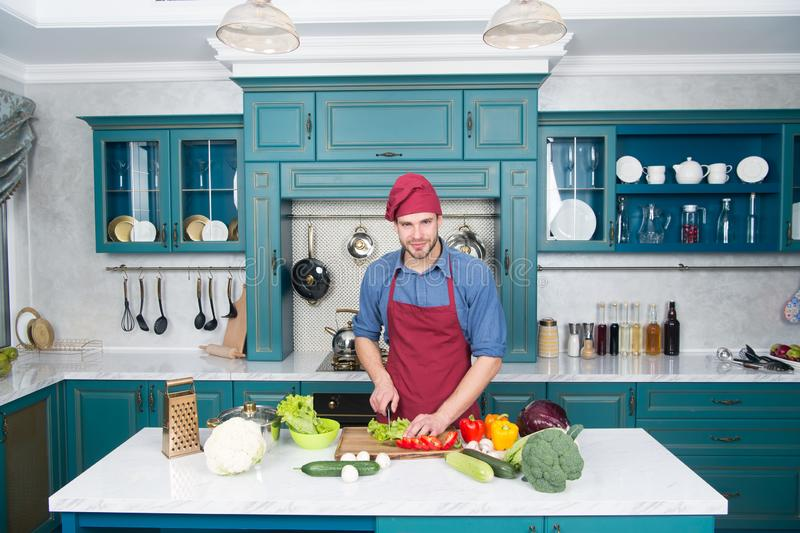 Man chef cooking in kitchen. Vegetable station chef in show kitchen. Man on dieting day. Think of what you put in your stock photo