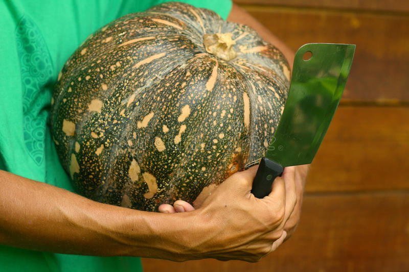 Man Chef Holding Pumpkin And Cleaver Knife Royalty Free Stock Images