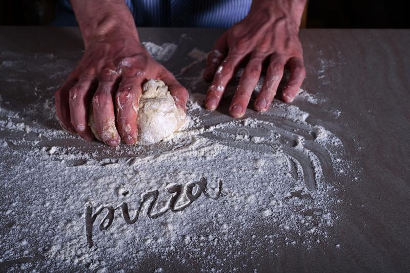 Man chef making dough for pizza. With word PIZZA on flour royalty free stock photography