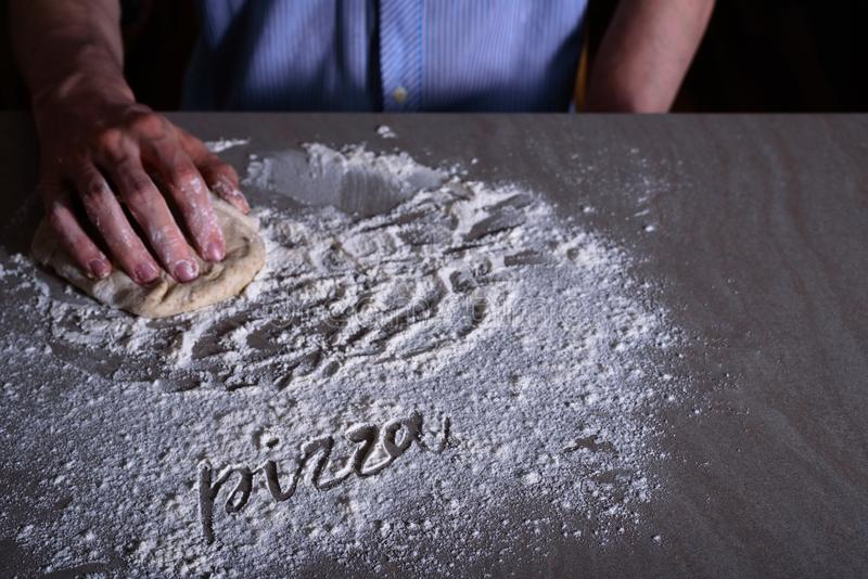 Man chef making dough for pizza. With word PIZZA on flour royalty free stock photo