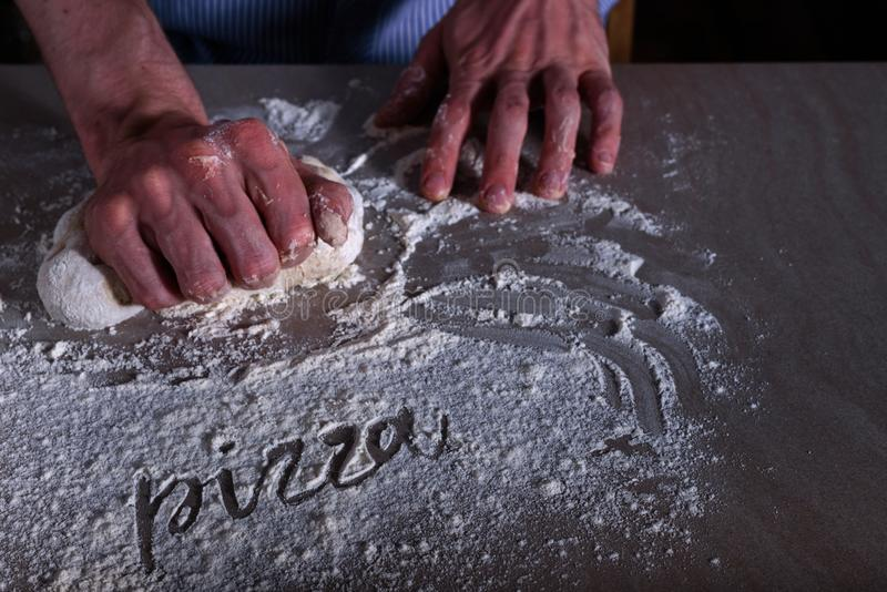 Man chef making dough for pizza. With word PIZZA on flour stock photography