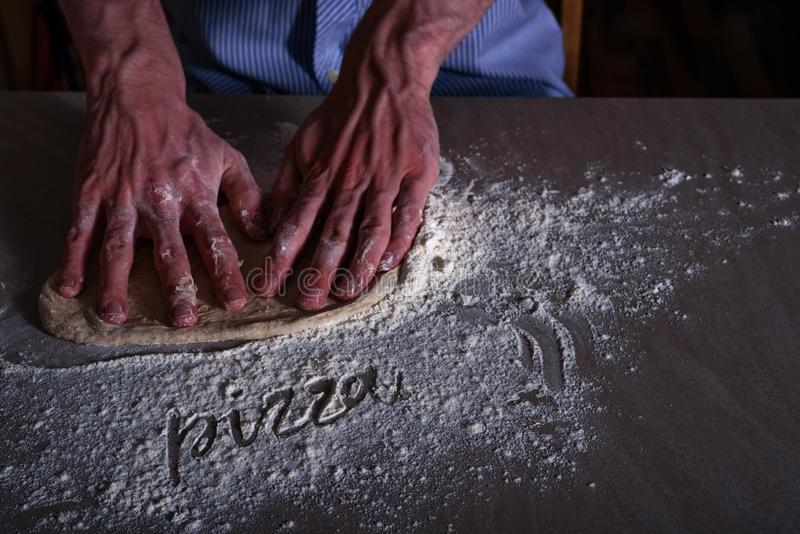 Man chef making dough for pizza. With word PIZZA on flour stock photo