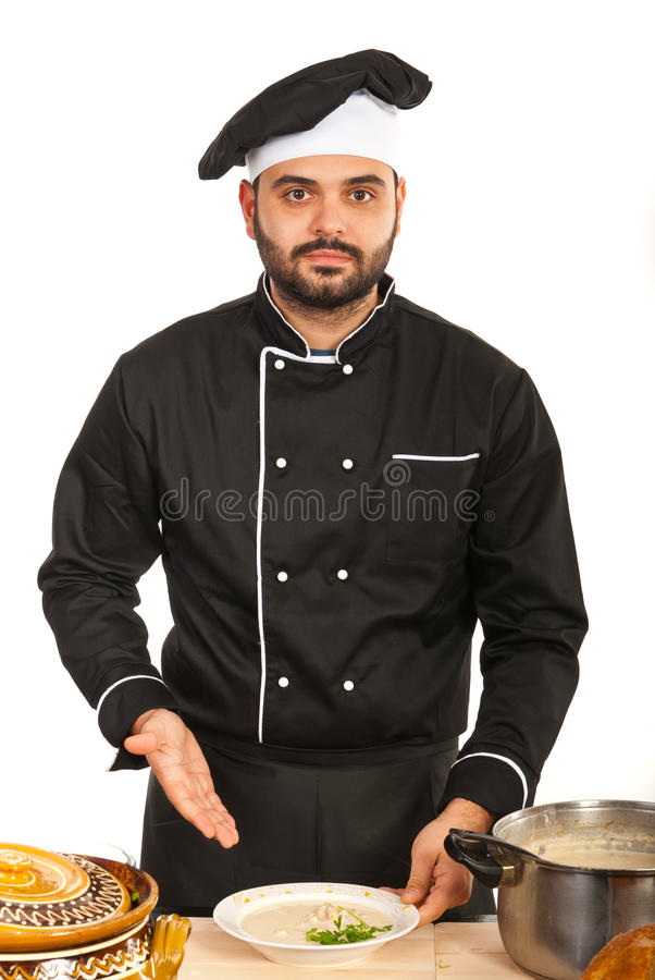 Man chef showing soup. Chef man showing soup on plate in kitchen stock photo