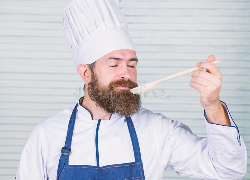 Man chef taste soup from wooden spoon. Cuisine culinary. Vitamin. Dieting organic food. Happy bearded man. chef recipe stock photography