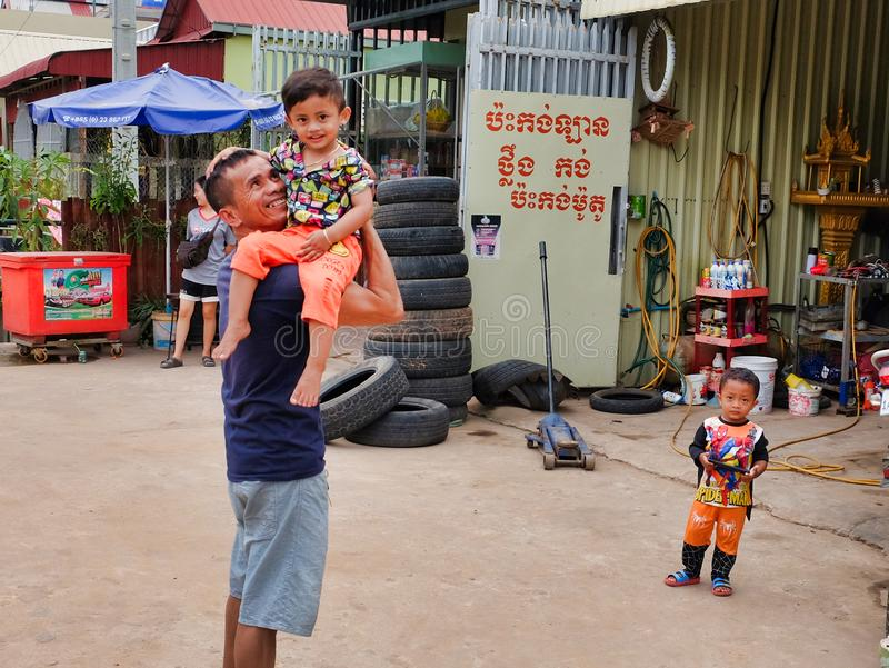 Man with a child in his arms near the tire shop, slums of Asia, residents of poor areas of the. Cambodia, Siem Reap 12/08/2018 a man with a child in his arms stock photo