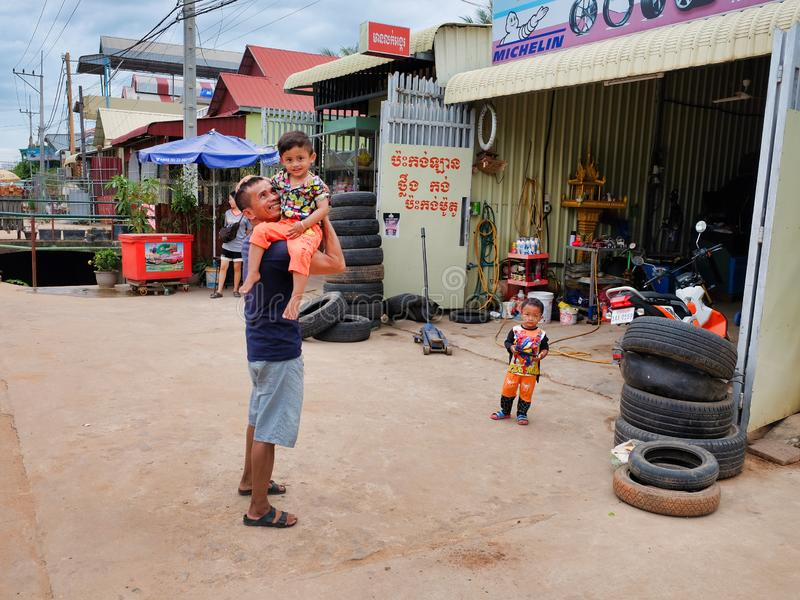 Man with a child in his arms near the tire shop, slums of Asia, residents of poor areas of the. Cambodia, Siem Reap 12/08/2018 a man with a child in his arms royalty free stock photography