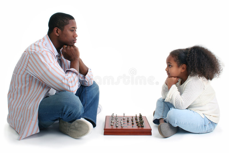 Man and Child Playing Chess. African American man and little girl playing chess. Sitting crossed-legged on either side of game and looking at each other. Shot in