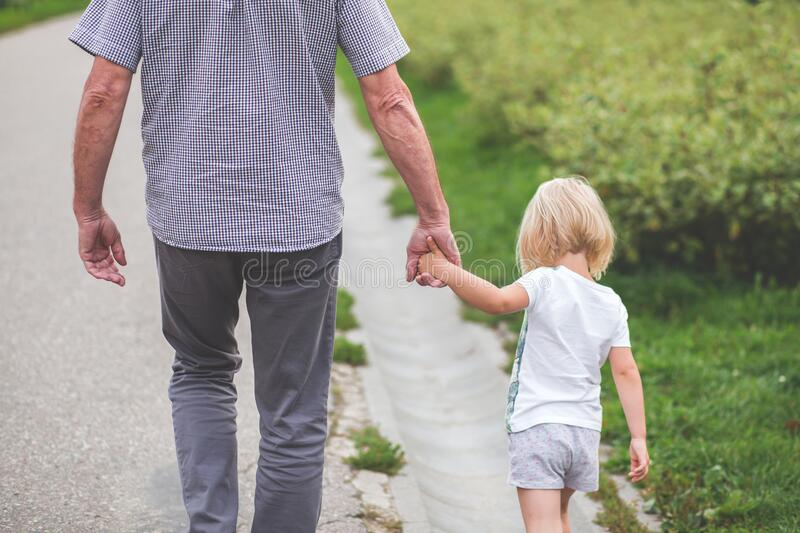 Man and Child Walking Near Bushes during Daytime stock photos