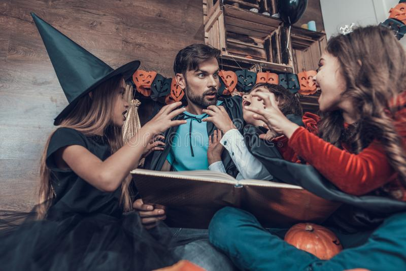Man and Children in Halloween Costumes having Fun royalty free stock image