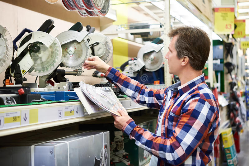Man chooses blade for electric miter saws in store stock images