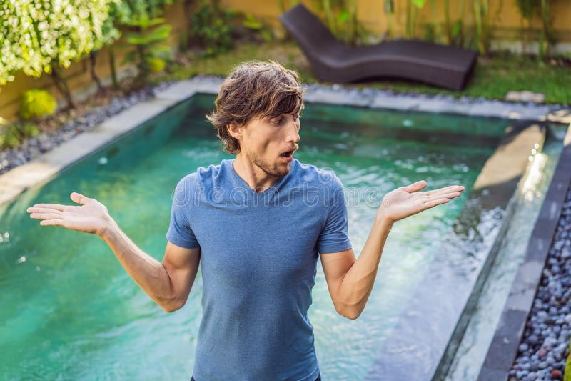 Man chooses chemicals for the pool. Swimming pool service and equipment with chemical cleaning products and tools.  royalty free stock image