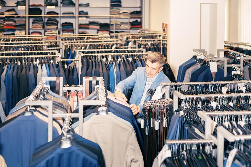 Man chooses clothes in a boutique. the store has a lot of jackets, belts. buying and choosing new clothes stock photo