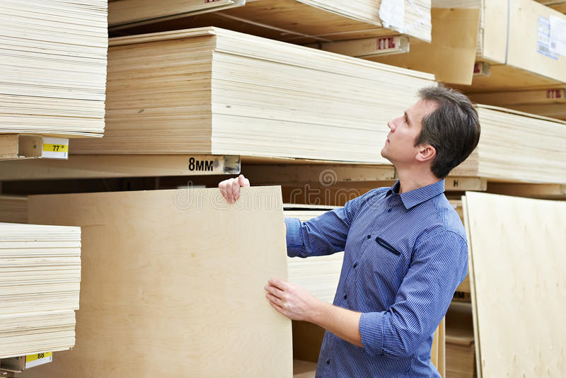 Man chooses plywood for construction in store. Man chooses plywood for the construction of the store royalty free stock image