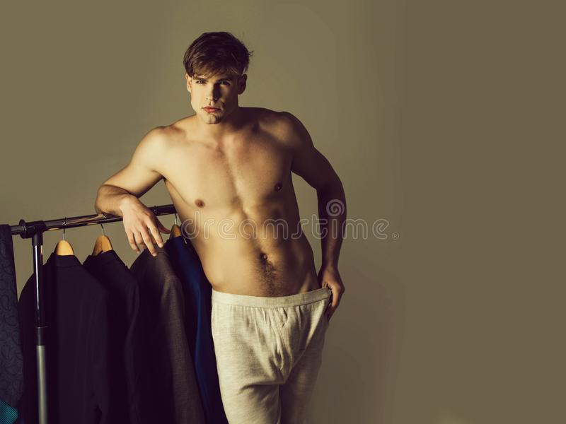 Man chooses shirt in the closet in underwear pants. On grey background, copy space stock image