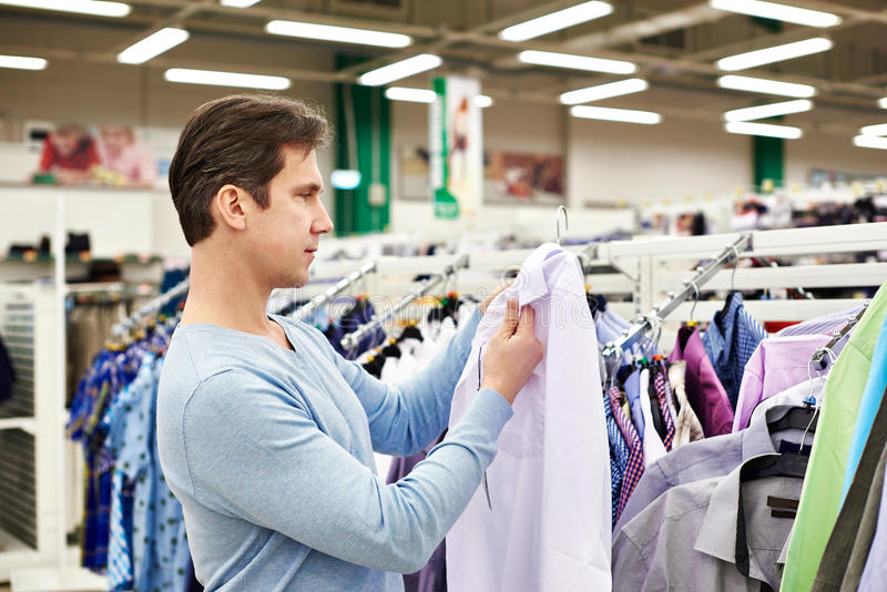 Man chooses a shirt in shop royalty free stock photos