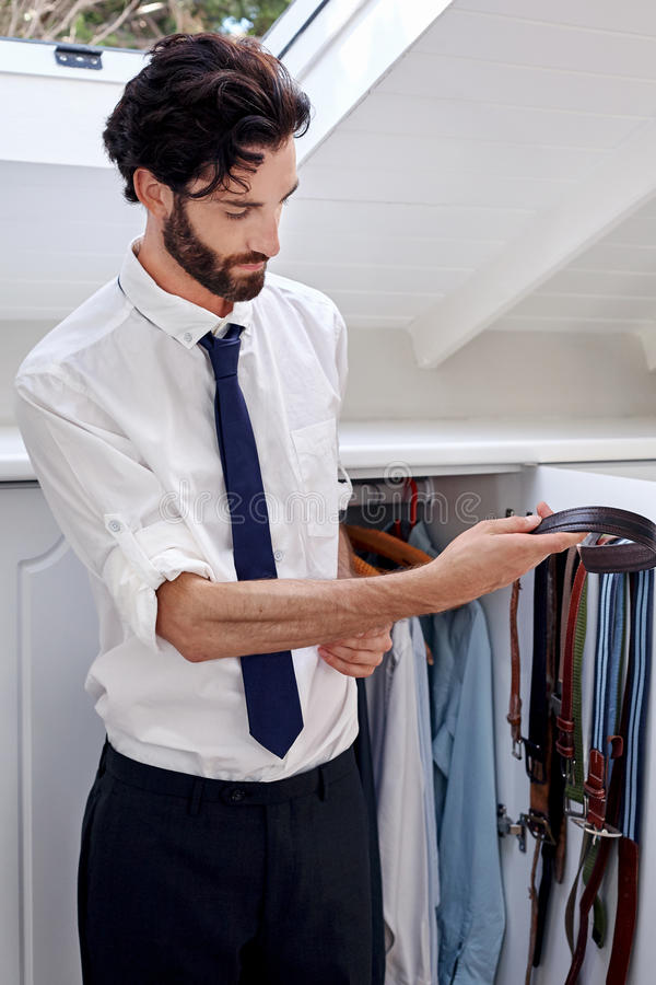 Man choosing belt. Professional man getting ready for work choosing belt from bedroom cupboard stock images