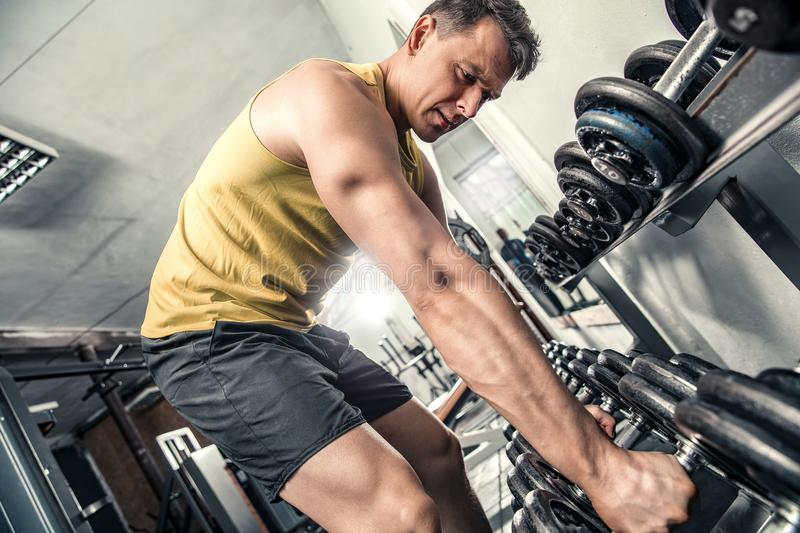 Man is choosing dumbbell stock images