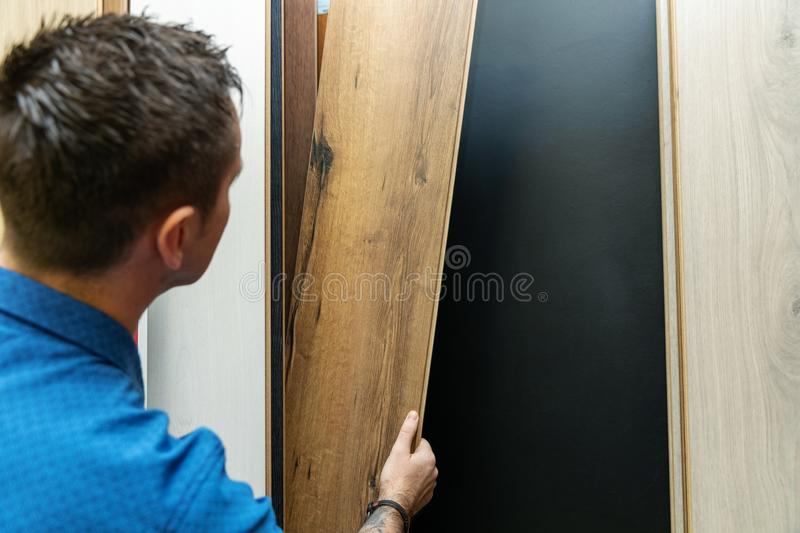 Man choosing floor laminate for his home in flooring store royalty free stock image