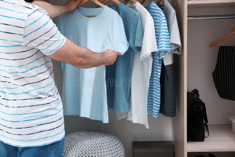 Man choosing outfit from large wardrobe closet with clothes, closeup. Man choosing outfit from large wardrobe closet with stylish clothes, closeup royalty free stock photos