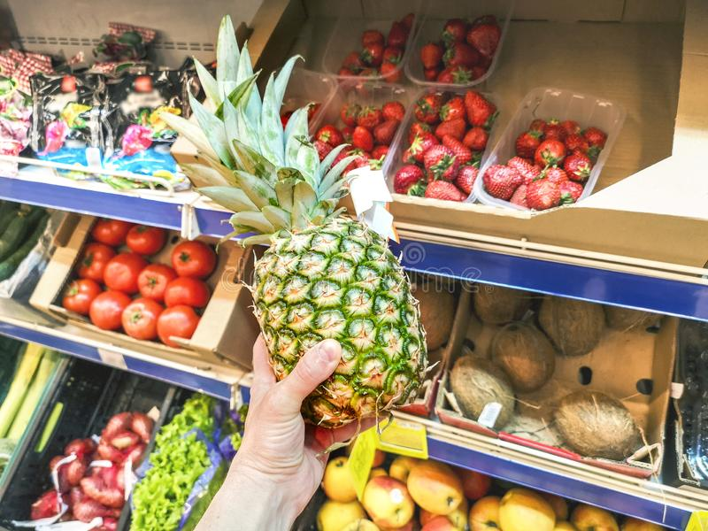 Man choosing pineapple during shopping at the supermarket. Man picking up, choosing fruits, pineapples stock photography