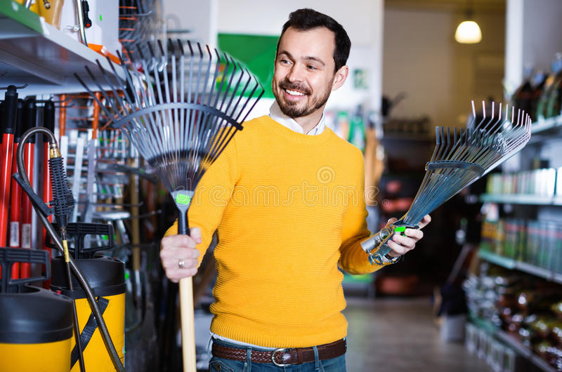 Man choosing various tools in garden equipment shop. Smiling positive man choosing various tools in garden equipment shop royalty free stock photography