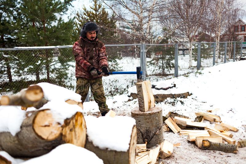 Man chopping wood in the winter royalty free stock images