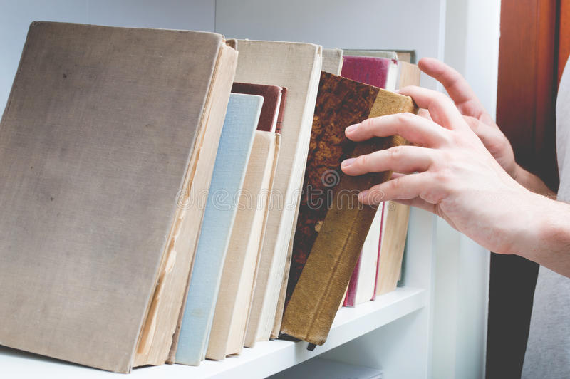 Man chose book from bookshelf. Image performed in vintage stylization royalty free stock photo