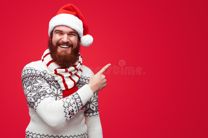 Man in christmas clothes pointing away at copyspace isolated over red royalty free stock photography