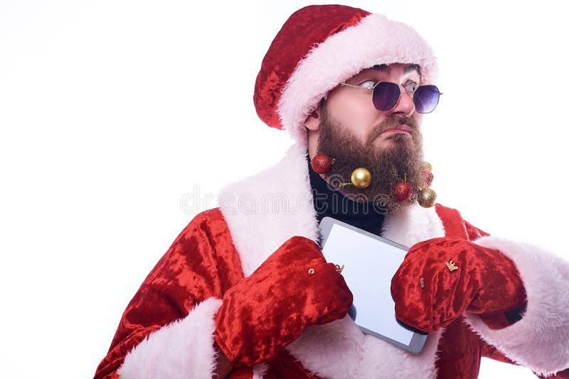 A man with Christmas toys in a beard and in a suit of Santa Claus hides the tablet in a fur coat stock photo