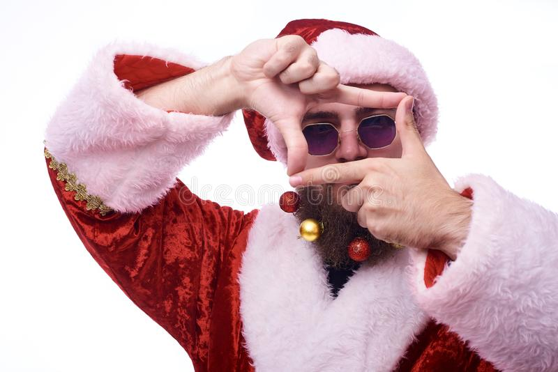 A man with Christmas toys in a beard and in a suit of Santa Claus holds hands in front of his face in the shape of a frame royalty free stock photo
