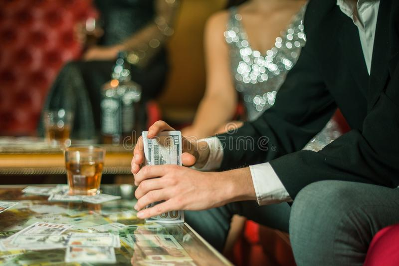 Man with cigar counting money in the club. Group of young multi-ethnic friends relaxing in shisha club-bar in rich stock photo
