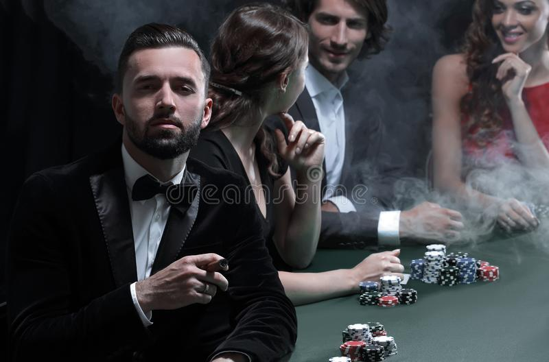 Man with cigar looking up from poker game in casino. Well-dressed group at poker table stock images