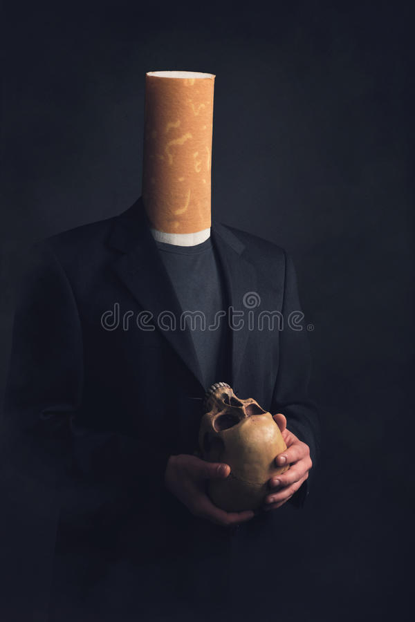 A man with a cigarette filter as a head holding a skull in his h royalty free stock photography