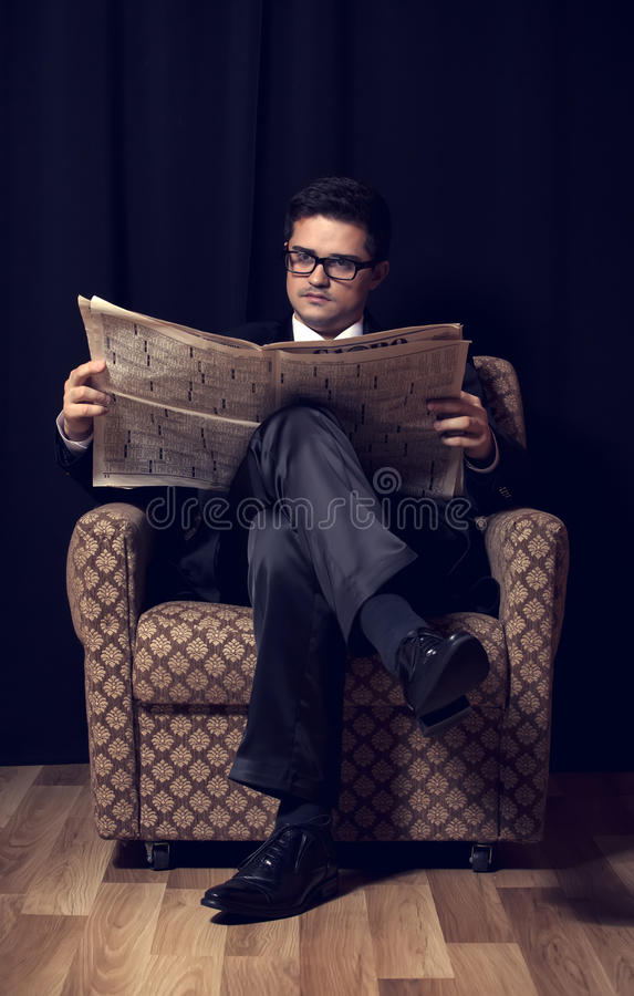 Download Man With Cigarette And Newspaper Sitting In Vintage Armchair Stock Image - Image: 29125211