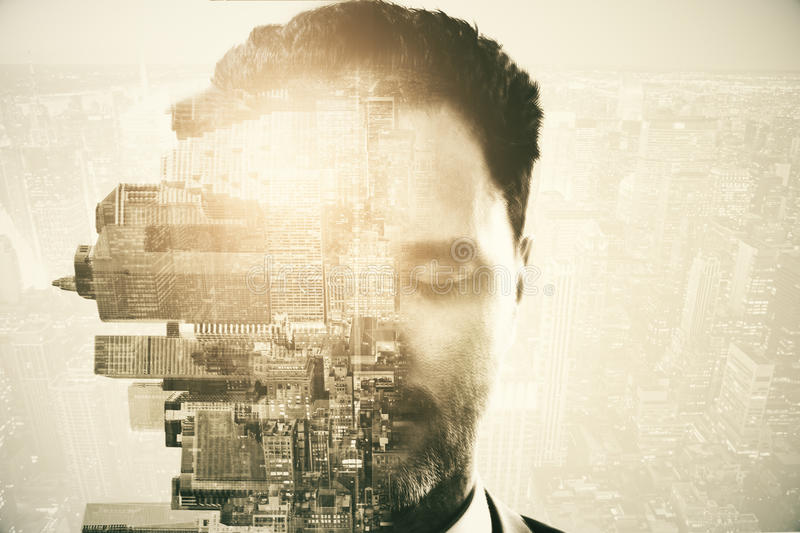 Man and city on abstract background. Half of caucasian man's face with closed eyes and rotated sideways city on abstract background with light. Double exposure stock photo