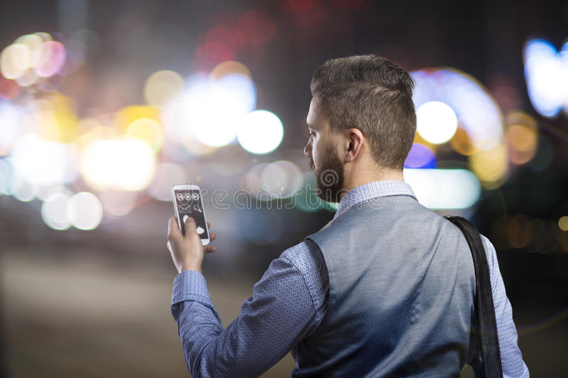 Man in the city. Handsome young hipster with his smartphone outside in the night city royalty free stock photos