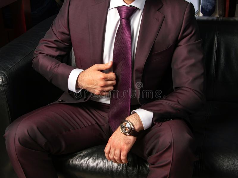 A man in a classic suit sits on a black leather sofa, close up royalty free stock photo