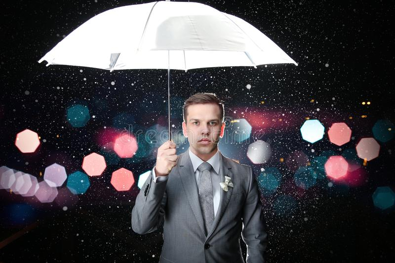 Man in classic suit with white umbrella in flash lights and rain drops royalty free stock photography