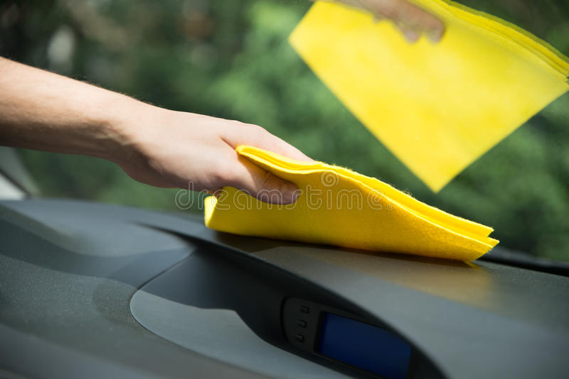 Man cleaning car interior with cloth. Man's hand cleaning car interior with yellow microfiber cloth royalty free stock photography